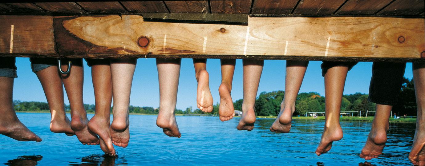 Kinderbeine baumeln von einem Holzsteg am See, Mecklenburgische Schweiz