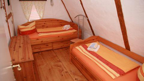 kleines Schlafzimmer mit rustikalem Dielenboden