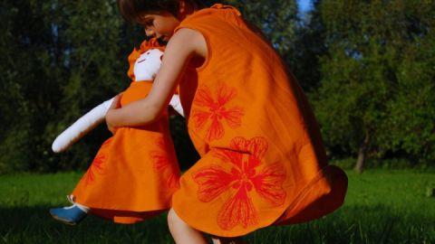 Mädchenkleid mit Stockrosen, dazu Puppe zum An- und Ausziehen